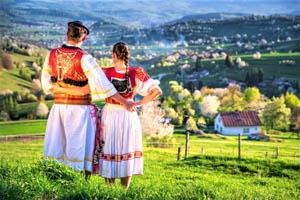 pár v kroji stojaci na lúke a pozerajúci sa na slovenskú dedinu